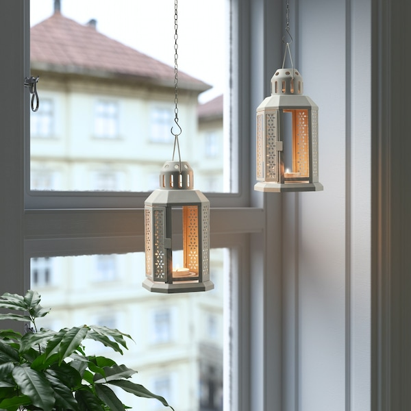 ENRUM lanterns hang in a window, suspended by chains, used as Diwali decorations.