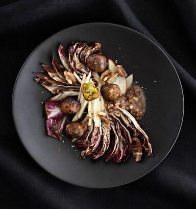 Ensalada de chicoria e noces con albóndegas vexetais servida nun prato de cor gris escuro, vista dende arriba.