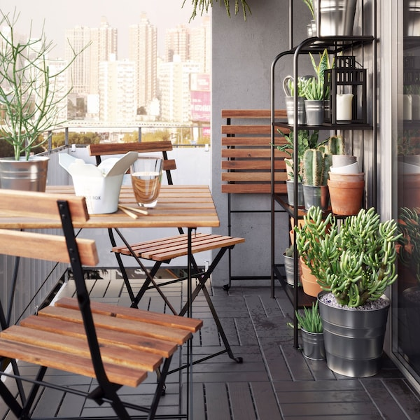 Ensemble avec table et deux chaises d'extérieur en acacia et en acier noir, sur un balcon avec des plantes.