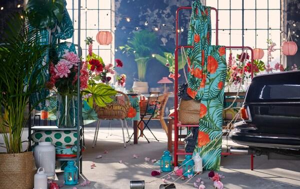 Ensemble intérieur industriel spacieux préparé pour une fête avec des textiles, des décorations, des plantes et l'extrémité d'une voiture avec des boîtes de conserve qui traînent en arrière.