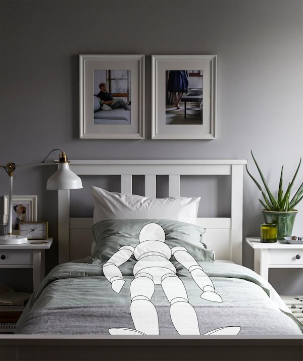 Enterijer spavaće sobe s nacrtanom osobom koja leži u ispruženom, simetričnom položaju, što se ogleda i u urednom enterijeru prostorije.