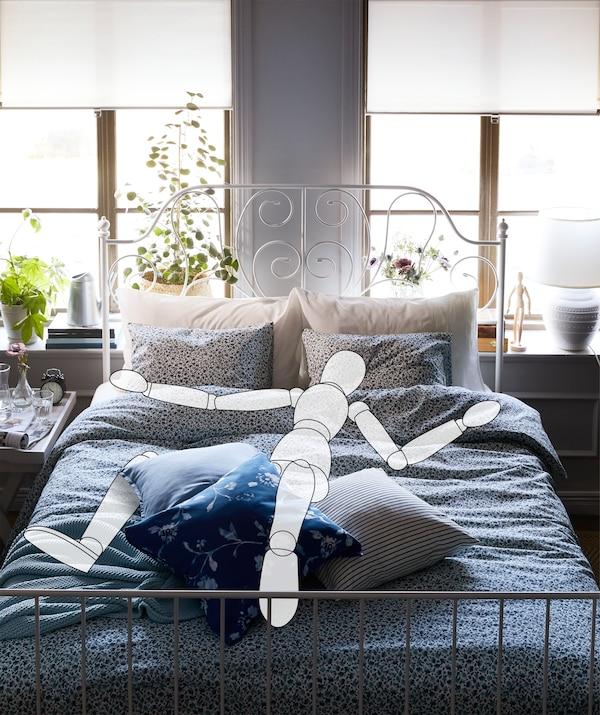 Enterijer spavaće sobe sa širokim krevetom pored prozora. Skica figure u ljudskoj veličini koja rašireno leži na krevetu.