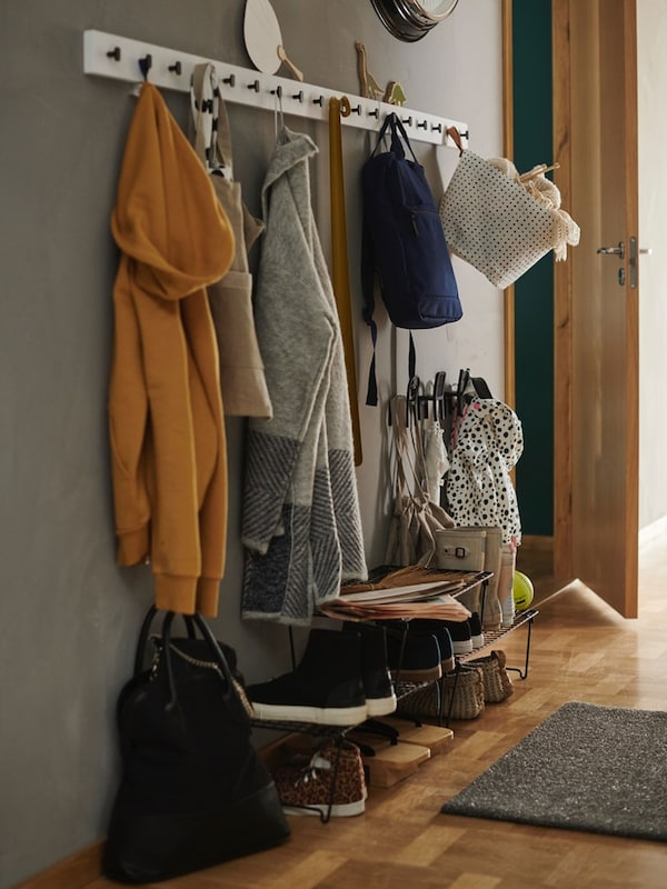 Entrance to family home with GREJIG shoe rack stacked with footwear and wall hooks holding jackets and bags