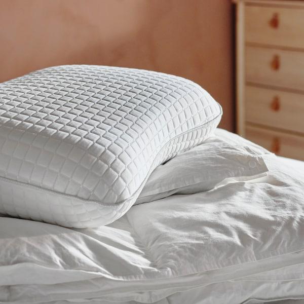 Ergonomiska kudden KLUBBSPORRE i säng med vita sängkläder.