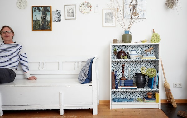 Erik sitting on a white bench against a white wall, next to a floral patterned bookcase filled with books and ornaments.