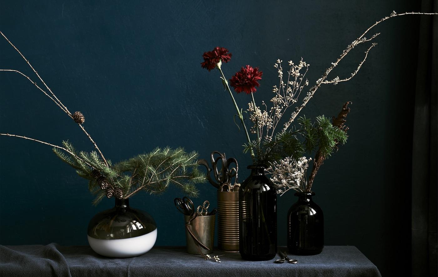Erikokoisia kukka-asetelmia erilaisissa maljakoissa tummaa taustaa vasten.