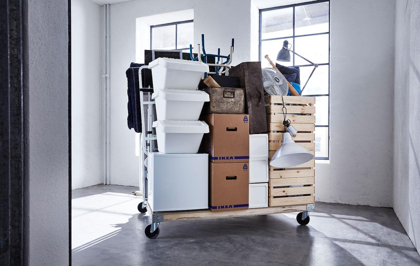 Erilaisia muuttotarvikkeita ja JÄTTENE-laatikoita pinottuna puiselle kuormalavalle pyörillä, tyhjässä huoneessa.