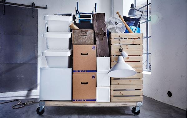 Erilaisia muuttotarvikkeita ja pahvisia muuttolaatikoita pinottuna puiselle kuormalavalle pyörillä, tyhjässä huoneessa.