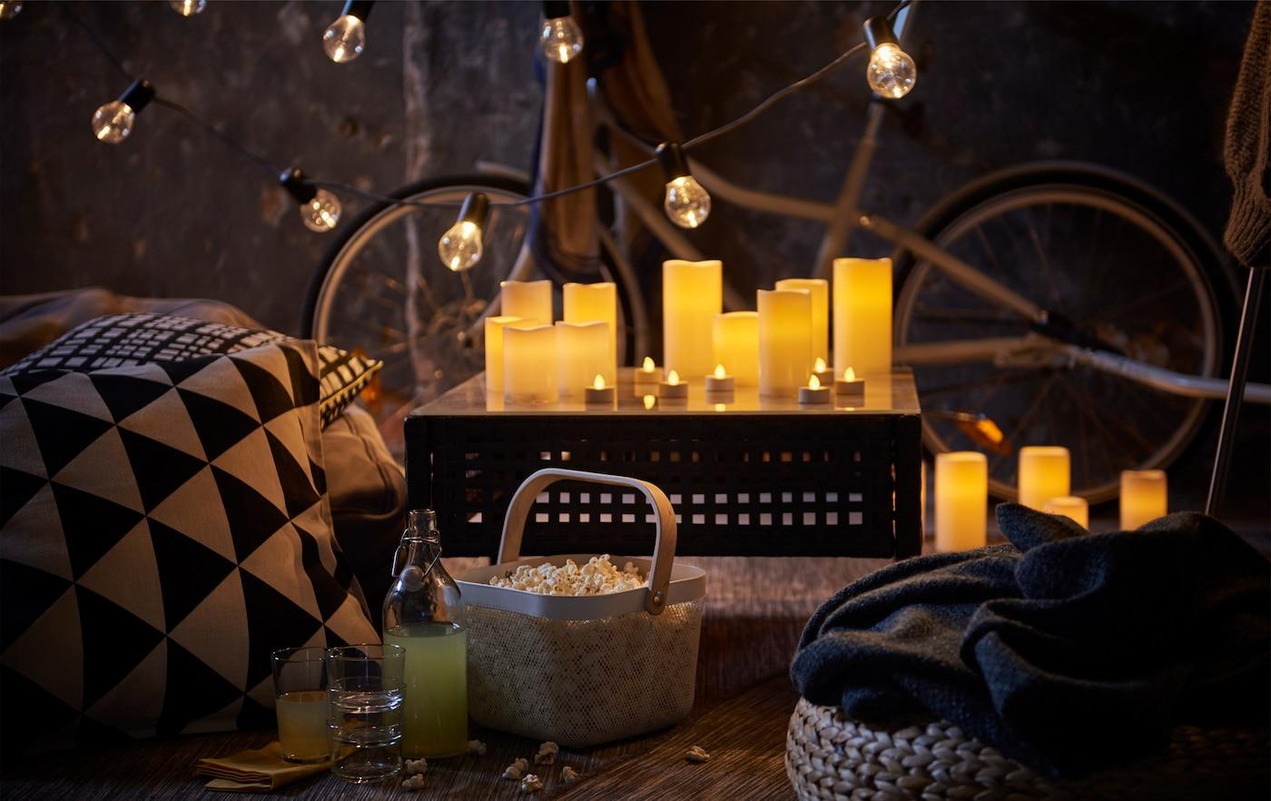 Erleuchtete Kerzen auf einem Tisch umgeben von gemusterten Kissen, Lichterketten, Essen und Trinken