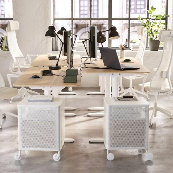Es ist ein offener Bürobereich zu sehen mit vier Drehstühlen, vier Schreibtischen, vier Arbeitsleuchten und zwei Schubladenelementen.