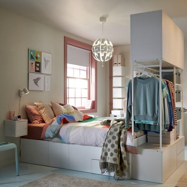 Es ist ein pastellfarbenes Studentenzimmer zu sehen, in dessen Mitte ein Bettgestell mit integrierter Aufbewahrung unter dem Bett und hängender Kleideraufbewahrung am Fußende des Bettes steht.