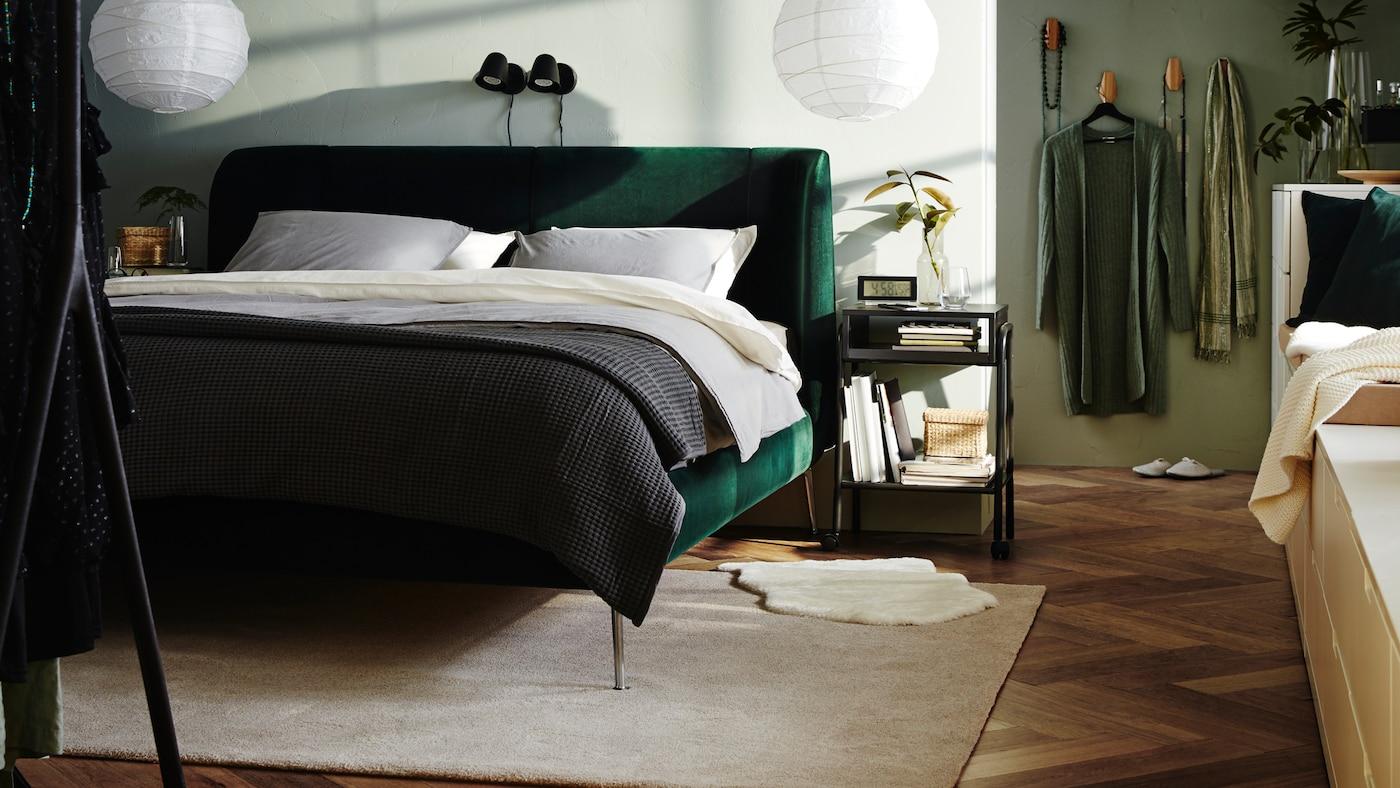 Es ist ein Schlafzimmer mit einem gepolsterten TUFJORD Bettgestell in Dunkelgrün, weißer Bettwäsche und einer grauen Tagesdecke und zwei weißen Hängeleuchtenschirmen zu sehen.