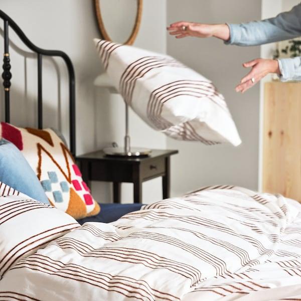 Es ist ein schwarzes SAGSTUA Bettgestell zu sehen, das mit SMALFRÄKEN Bettwäsche in Weiß mit braunen Streifen bezogen ist. Eine Person wirft gerade ein Kopfkissen auf das Bett.