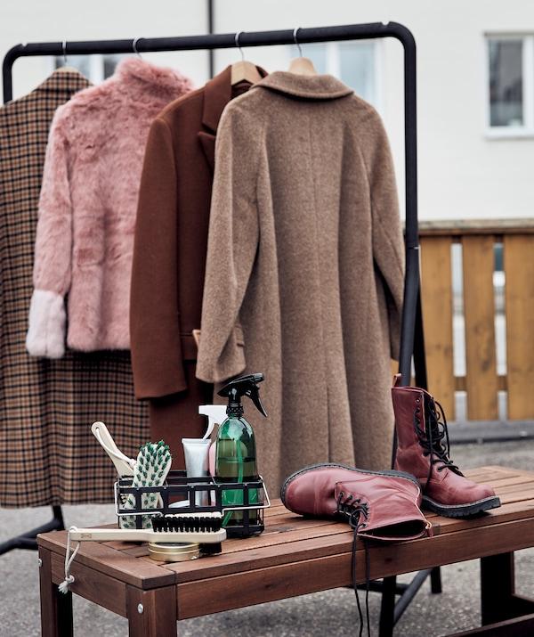 Es ist ein TURBO Kleiderständer mit Winterkleidung daran im Freien zu sehen. Daneben steht eine Bank mit einem Paar Schuhe und einem Reinigungs-Set darauf.