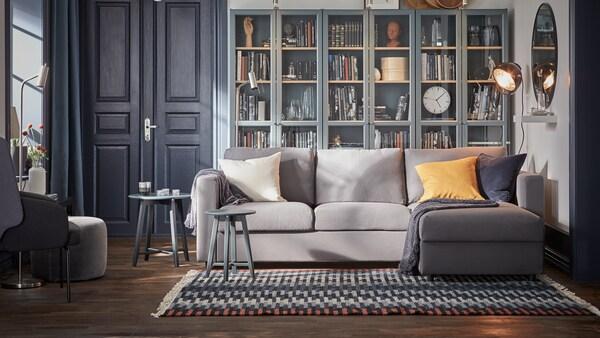 Es ist ein Wohnzimmer mit einem großen Teppich vor dem Sofa zu sehen.