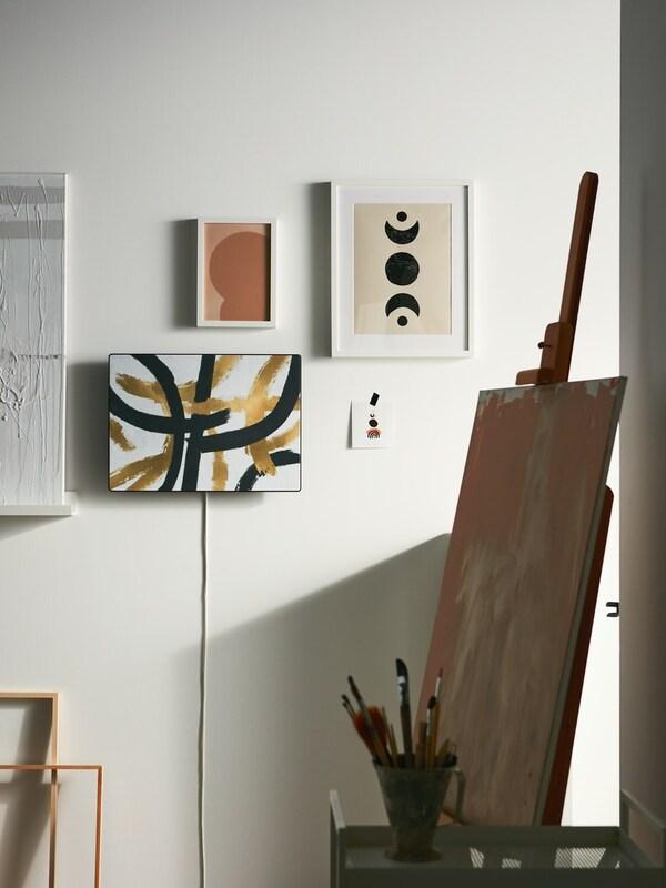 Es ist eine Nahaufnahme eines SYMFONISK Paneels für Rahmen mit Speaker mit einem Schallplattendesign in Dunkellila und Rot zu sehen, das auf dem Boden steht.