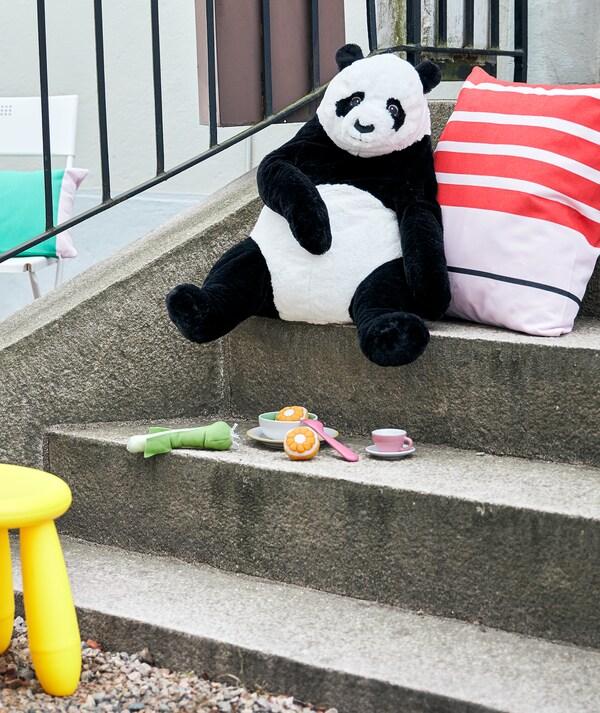 Escalier extérieur avec un panda en peluche accoté contre un coussin, comme s'il avait mangé dans la vaisselle jouet en dessous.