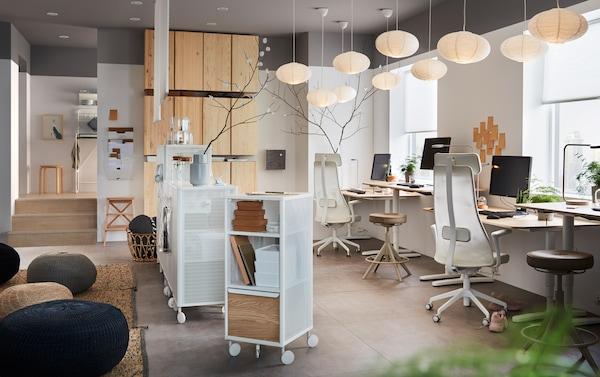 Escritório equipado com cadeiras giratórias ergonómicas JÄRVFJÄLLET, armários de arrumação em pinho IVAR e secretárias em chapa de carvalho BEKANT.