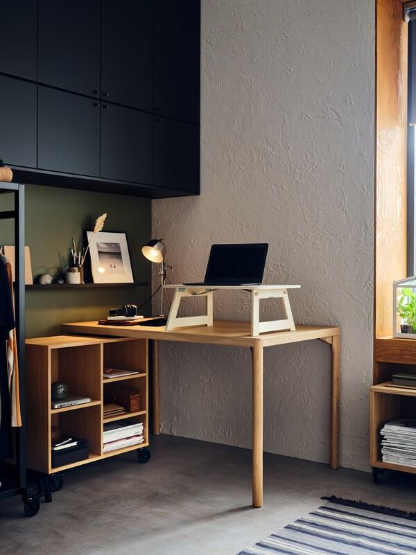 Escritorio formado por una mesa y una estantería con ruedas RÅVAROR. Encima de la mesa hay un portátil.