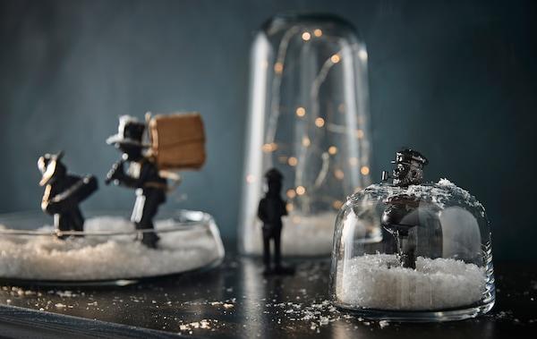 Esferas de nieve caseras hechas con tarros y jarrones de cristal de IKEA, con luces, nieve falsa y figuras en el interior.