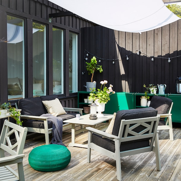 Espace extérieur avec canapé, fauteuils et table basse BONDHOLMEN en gris. Un pouf rond de couleur vert foncé est posé au sol.