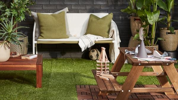 Espacio al aire libre en el que el suelo de exterior RUNNEN, de césped artificial y madera, forma diferentes zonas para comer y descansar.