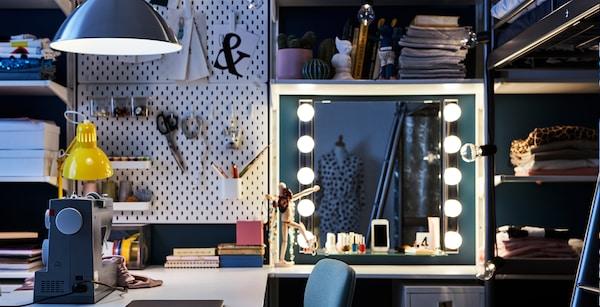 Espacio de trabajo en un dormitorio con un escritorio, máquina de coser, tocador y tablero perforado IKEA SKÅDIS.
