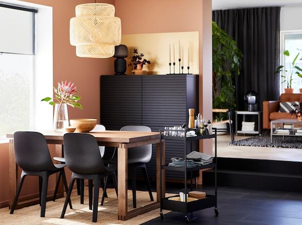 Espaço de refeição com cadeiras em antracite, uma mesa em chapa de madeira de carvalho maciça, módulo de arrumação em preto, um tapete em juta e um candeeiro suspenso em bambu.