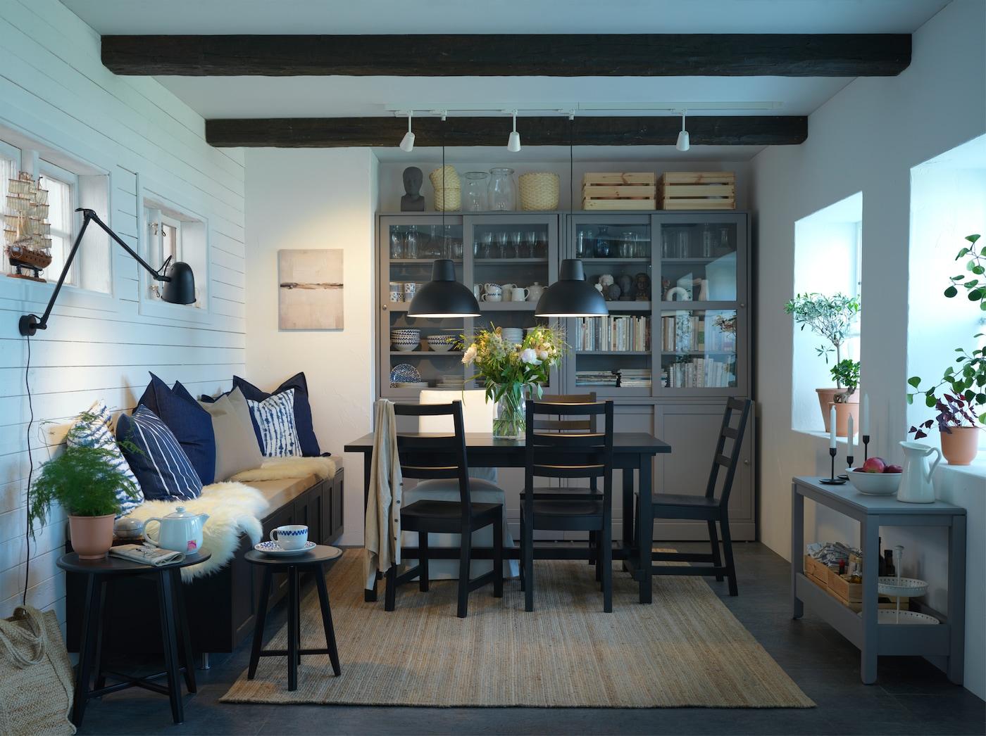 Espaço de refeição com uma mesa e cadeiras em preto, um tapete em juta, candeeiros suspensos em preto e uma combinação de arrumação em cinzento com portas deslizantes.