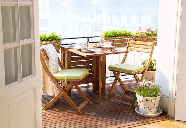 Espaço exterior com uma mesa grande preparada para uma refeição, cadeiras e um grande guarda sol.