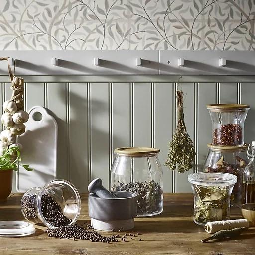 Especias en tarros de vidrio con tapas de madera en una encimera y hierbas colgando de ganchos.