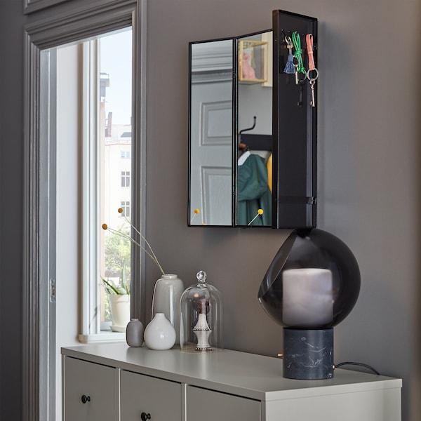 Espejo KARMSUND montado en la pared; en la parte posterior de los espejos laterales ajustables, hay unas llaves colgando de los ganchos.