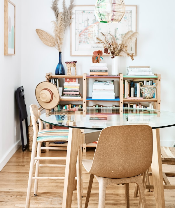 Essbereich mit einem Esstisch mit Glastischplatte und ODGER Stühlen braun vor einer weißen Wand, an der ein Regal steht.