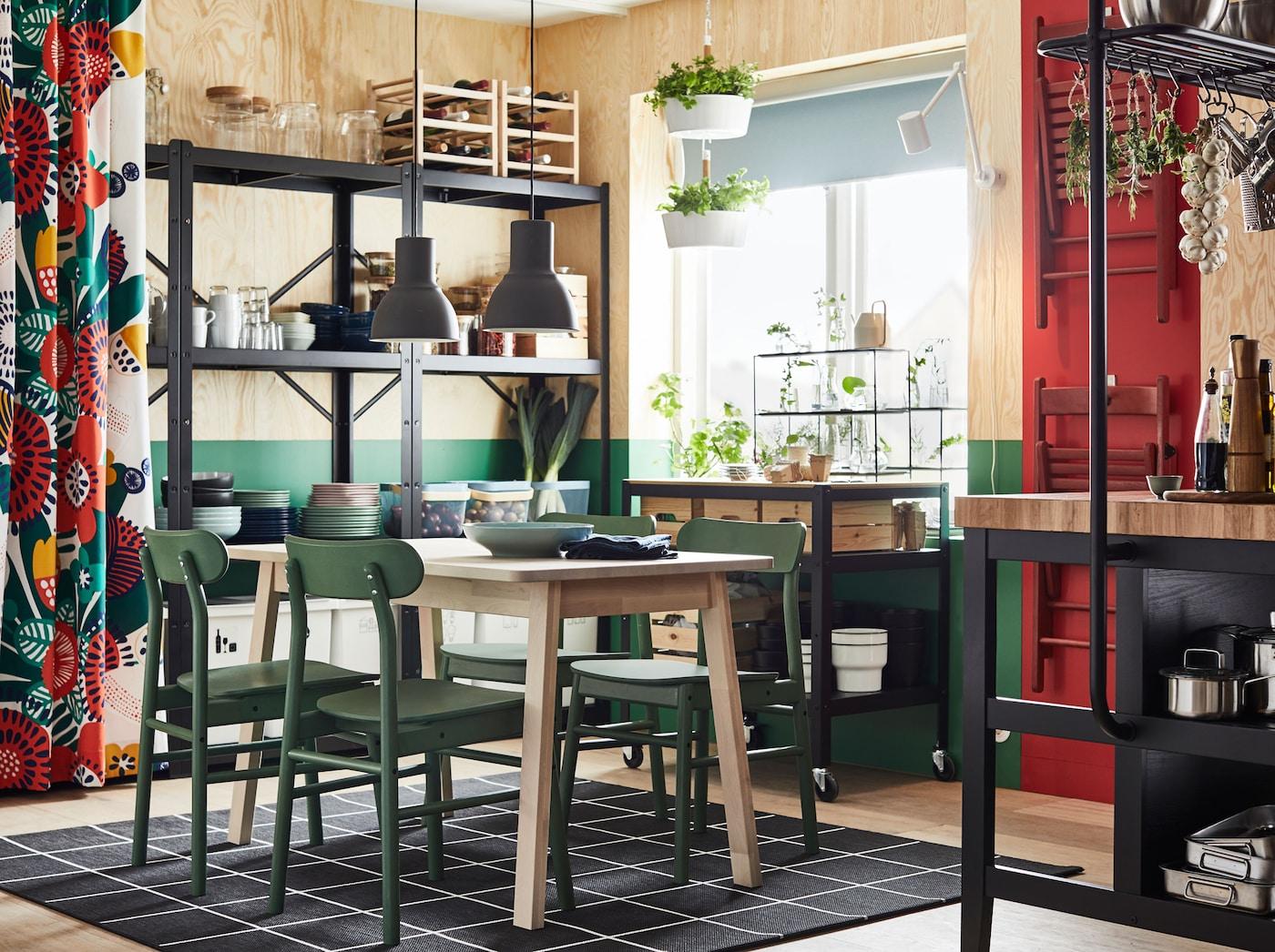 Esszimmer mit gemusterten Vorhängen, Holztisch, grünen Stühlen & hellbraunen Wänden.