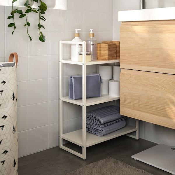 Estante metálico no baño con toallas e accesorios