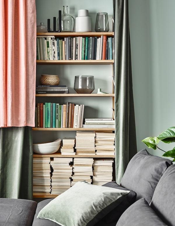 Estantería abarrotada con libros y decoraciones parcialmente escondidas con una cortina en un salón.