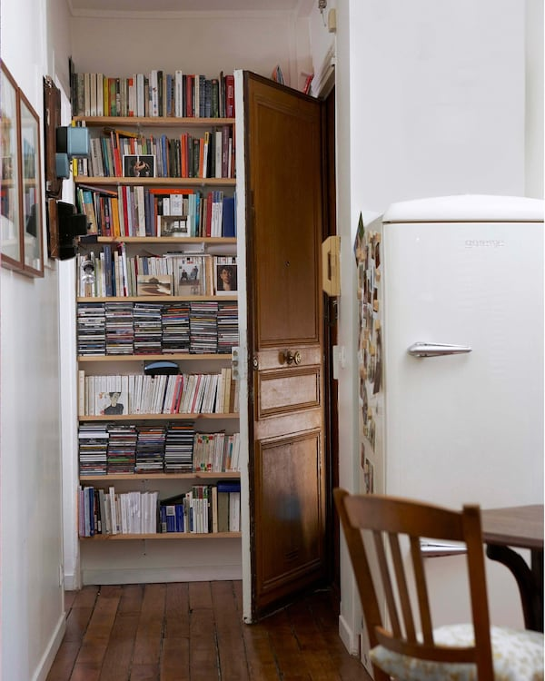 Estantería abierta detrás de una puerta abierta.