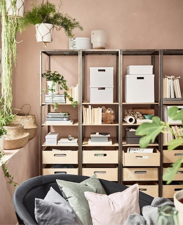Estanterías VEBERÖD una junto a otra en acero y abedul crean espacios de almacenamiento y orden en este salón rosa.