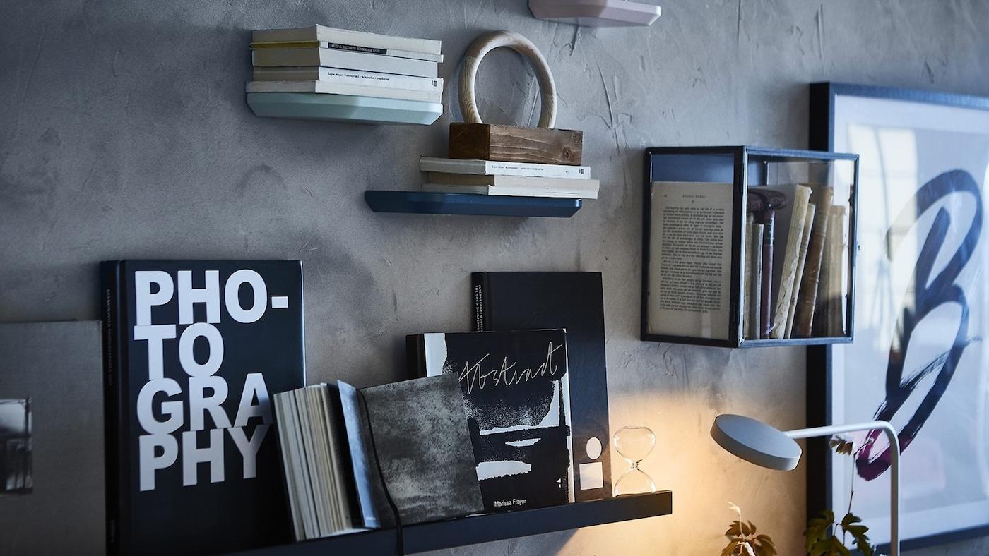 Estantes con libros y mini vitrina sobre un muro oscuro