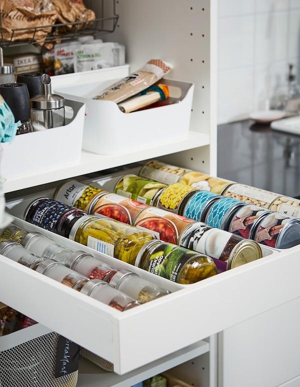 Estantes y un cajón abierto en un armario de cocina con latas, especias y tarros perfectamente organizados.