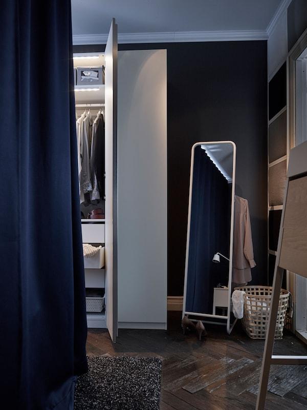 Este armario de dormitorio blanco con luces incorporadas está junto a un espejo con almacenaje para ropa.