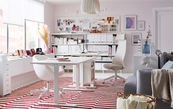 Este escritório em tons de branco tem  um tapete de tecelagem plana STOCKHOLM às riscas vermelhas e brancas, com um módulo de arrumação BEKANT e um bloco de gavetas GALANT em branco, ambos com rodízios.