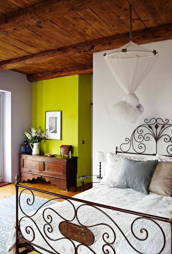 Estructura de cama de hierro forjado en un dormitorio rústico con techo de madera.