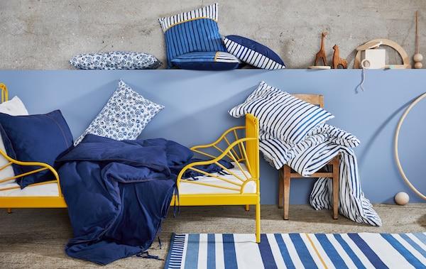 Estructura de cama MINNEN con ropa de cama azul y blanca con estampado de rayas y flores, cojines y juguetes de madera junto a una pared azul.