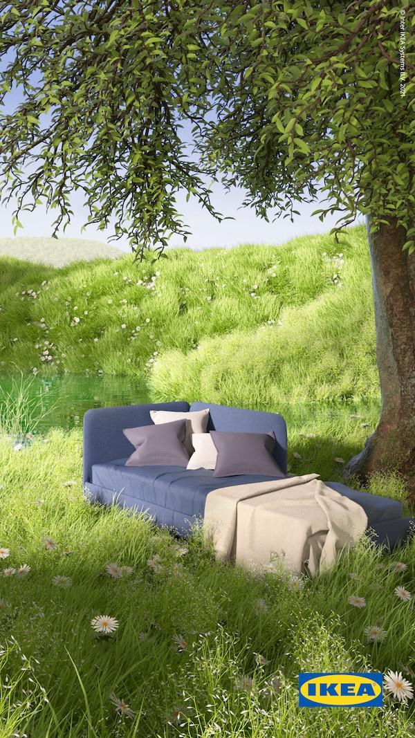 Estrutura de cama BLÅKULLEN em azul com cabeceira de cama de canto, uma manta e almofadas no topo, sobre uma relva verde exuberante junto a um lago.