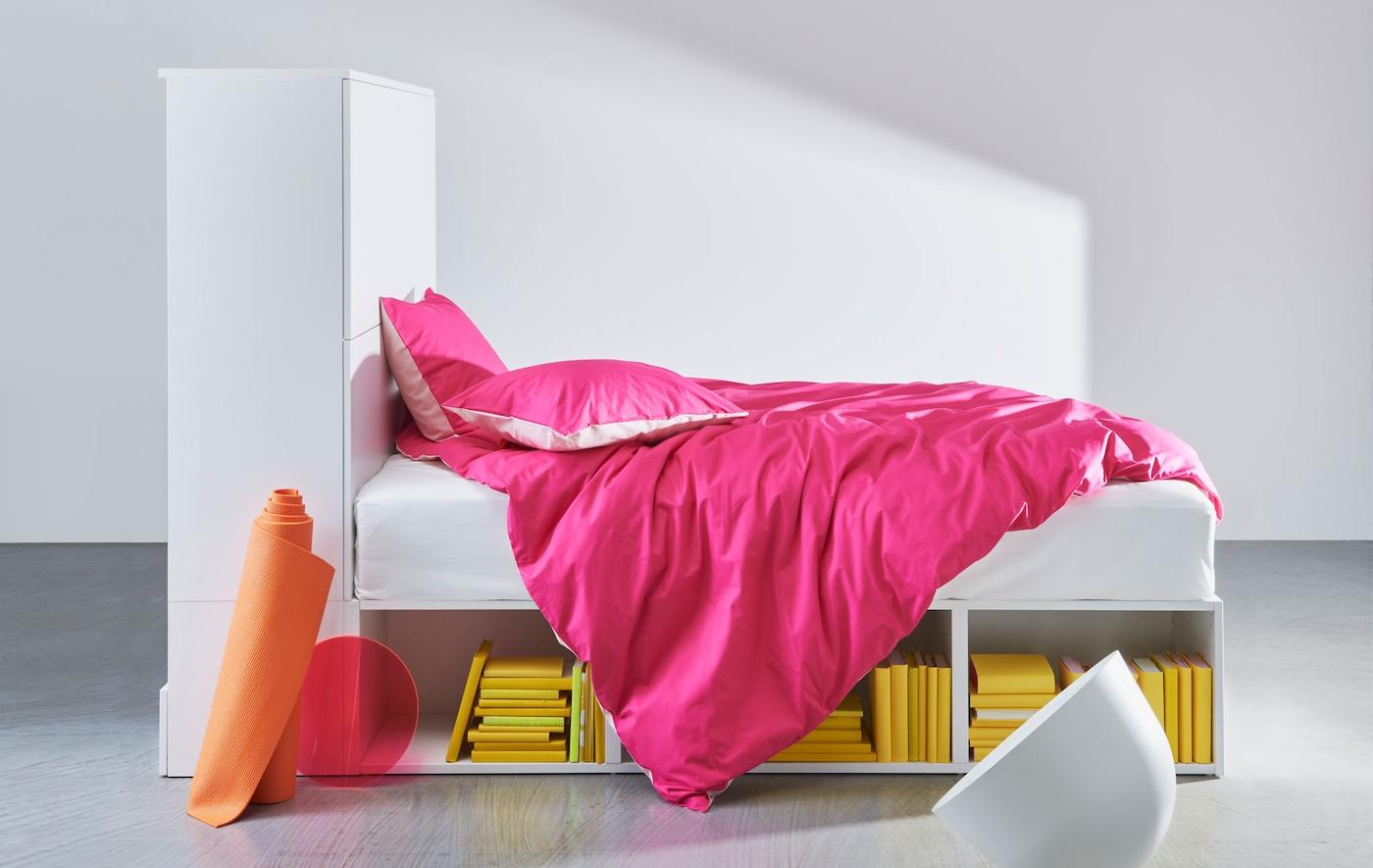 Estrutura de cama em branco com arrumação integrada e com roupa de cama cor de rosa.