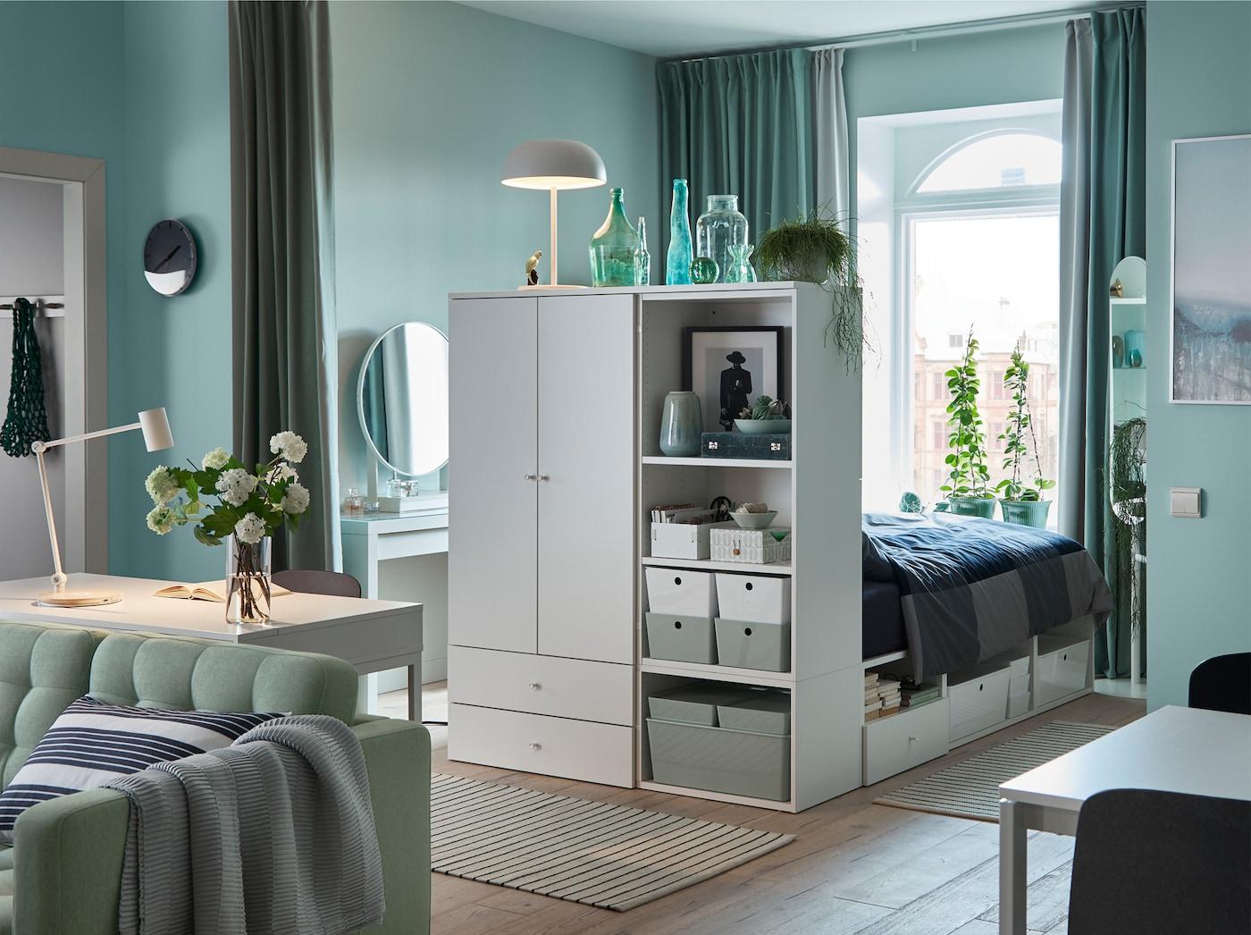 Estúdio em verde claro, ambiente calmo, com cortinados verdes, um sofá verde e uma estrutura de cama em branco com arrumação.