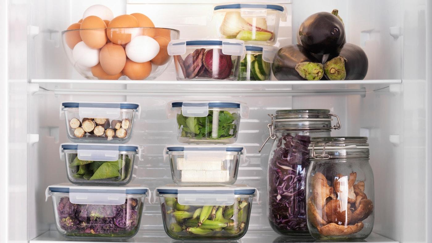 Et åbent køleskab med masser af gennemsigtige beholdere med forskellige madvarer i.