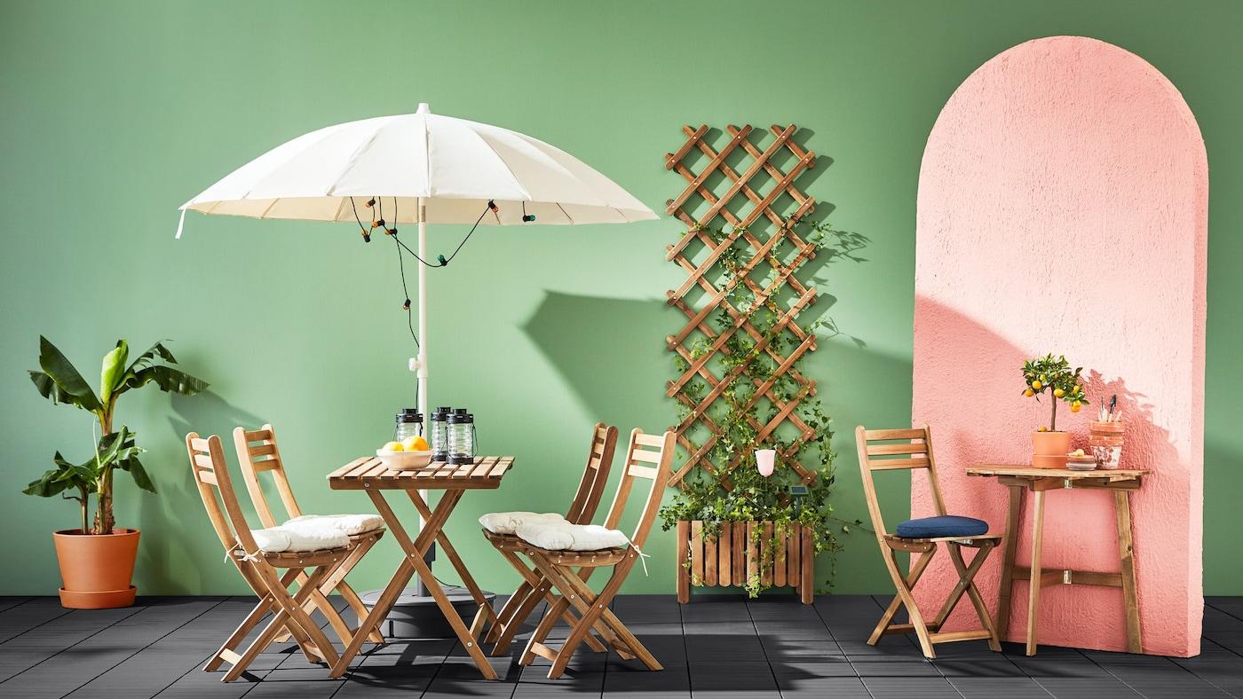 Et altansæt med fire stole og et bord der står i en opstilling med en parasol og et ekstra lille bord med en stol fra samme serie.