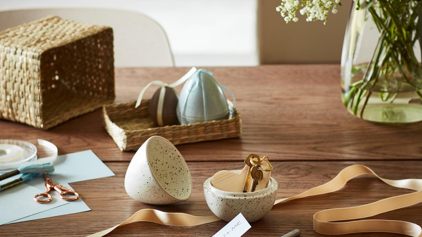 Et åpent RÅDFRÅGA egg med en nøkkel i, sammen med andre egg og en vase med hvite blomster, på et trebord.